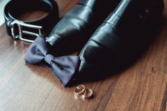 Black bow tie lies before leather shoes and belt. Grooms wedding morning Stock Photo