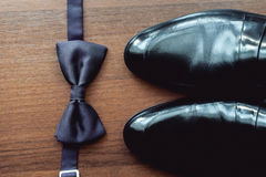 Black bow tie lies before leather shoes and belt. Grooms wedding morning Stock Image