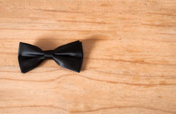 The black bow tie on wooden background Stock Photo