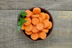 Black bowl with cut carrots fit on wooden background. Black bowl with cut carrots fit on wooden table Stock Photo