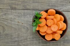 Black bowl with cut carrots fit on wooden, detail. Black bowl with cut carrots fit on wooden table Royalty Free Stock Photo