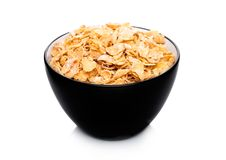 Black bowl with natural organic granola cereal. Corn flakes on white Royalty Free Stock Photography