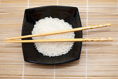 Black bowl with rice and chopsticks Royalty Free Stock Images