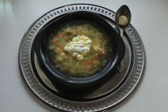 Black bowl of soup and spoon on a tray Royalty Free Stock Image