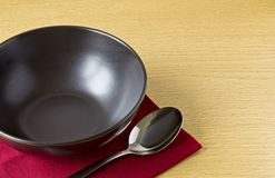Black bowl with spoon on table Royalty Free Stock Photography