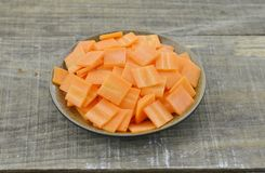 Black bowl with thin slices carrots on wooden table. Closeup Royalty Free Stock Photography