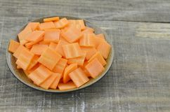 Black bowl with thin slices carrots on wooden table. Closeup Royalty Free Stock Image