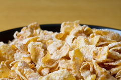 Black Bowl With Frosted Cereal Flakes Royalty Free Stock Images
