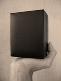 Black Box. A hand holding a black box. (Sepia stock photo
