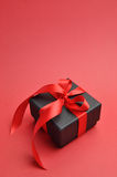 Black box romantic gift with red ribbon, vertical with copy space. Royalty Free Stock Photography