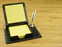 Black box and yellow paper note. Place on left with wood background Royalty Free Stock Images