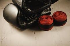 black boxing gloves and red bandage     black boxing gloves and red bandage on a stone background stock image