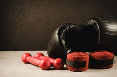 black boxing gloves and red dumbbells and bandage/sport concept with black boxing gloves and red dumbbells and bandage stock photography