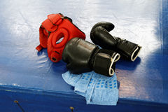 Black boxing gloves and red protective headgear stock photos