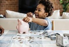 Black boy collecting money to piggy bank Stock Photo
