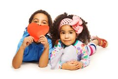 Black boy, girl and heart. Black boy laying with little girl with frizzy hair holding red heart made of paper Royalty Free Stock Photos