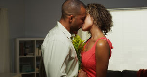 Black boyfriend surprises girlfriend with flowers Royalty Free Stock Photo