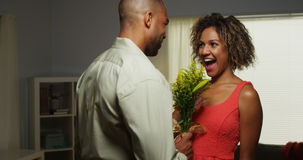 Black boyfriend surprises girlfriend with flowers. At home royalty free stock image