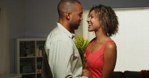 Black boyfriend surprises girlfriend with flowers stock images