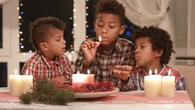 Black boys light Christmas candles. Children lighting red Christmas candles. Christmas eve at home. Happy holidays with brothers
