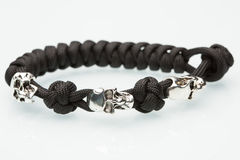 Black braided bracelet with skulls on white Royalty Free Stock Photo