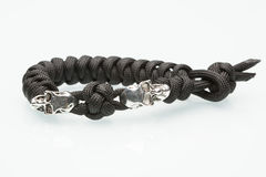 Black braided bracelet with skulls on white Stock Photography