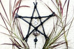 Black Branch Pentagram symbol for Witchcraft, Wicca, Paganism with selenite, smoky quartz and snowflake obsidian. Against cream background royalty free stock photo