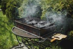 Black brazier with smoking coals in summer garden stock image