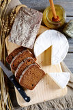 Black bread with brie cheese on a cutting board Stock Images