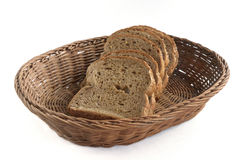 Black bread with cereals lying in a wicker basket. Isolated on white background Royalty Free Stock Photo