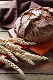 Black bread on a cutting board with ears of wheat Royalty Free Stock Photos
