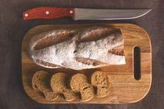 Black bread on a cutting board with a knife Stock Photography