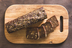 Black bread on a cutting board. Black bread with seeds is cut on a cutting board with a knife on a wooden background Stock Photography