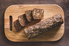 Black bread on a cutting board. Black bread with seeds is cut on a cutting board with a knife on a wooden background Stock Photo