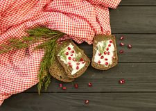 Black bread with grenades berries on a black wooden background. Christmas food, Christmas decorations with lemon, juniper, branch. Red berries Stock Images
