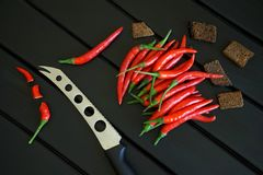 Black bread rusks, red chilli pods and a vegetable and cheese knife lie on a black wooden rustic table. Daylight stock photos