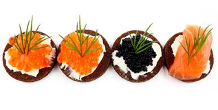 Black bread topped with salmon, trout and sturgeon caviar Royalty Free Stock Photo