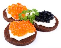 Black bread topped with salmon, trout and sturgeon caviar Stock Image