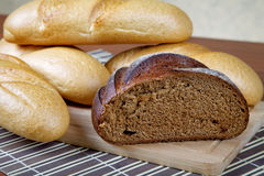 Black bread and white rolls on a  table Royalty Free Stock Photos