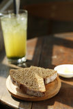Black bread on wooden plate iwth juicy fruit on the table Stock Image