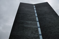 Black brick façade. Of a building with window elements on a rainy day stock photo