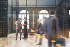Black brick and glass office, meeting room, people. People in a black brick conference room interior with loft windows, a wooden floor, aquarium like walls and Royalty Free Stock Photo