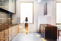 Black brick kitchen with bar, side view, woman royalty free stock images
