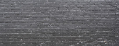 Black Brick Wall. A brick wall constructed from rows of retangular bricks and painted black Stock Image