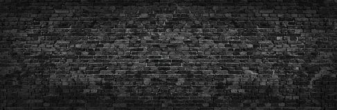 Black brick wall of panoramic view in high resolution. Panorama of black brick wall for site caps as background Stock Photos