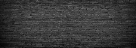 Black brick wall of panoramic view in high resolution. Panorama of black brick wall for site caps as background royalty free stock photo