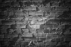 Black brick wall with spot illumination, texture. Black brick wall with spot illumination, frontal flat detailed background texture Royalty Free Stock Images