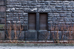 Black brick wall with two closed windows - background Stock Photography