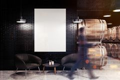 Black brick wine cellar, armchairs and poster, man stock photography