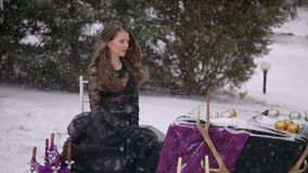 Bride in a black dress. Gothic wedding. Winter. The black bride. The bride in a black dress sits outdoors in the winter with a heavy snowfall near a decorated stock footage